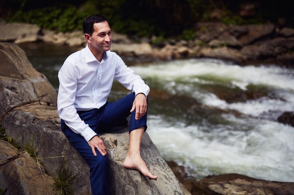 Sesja plenerowa w Bieszczadach pan mlody na kamieniu nad rzeka